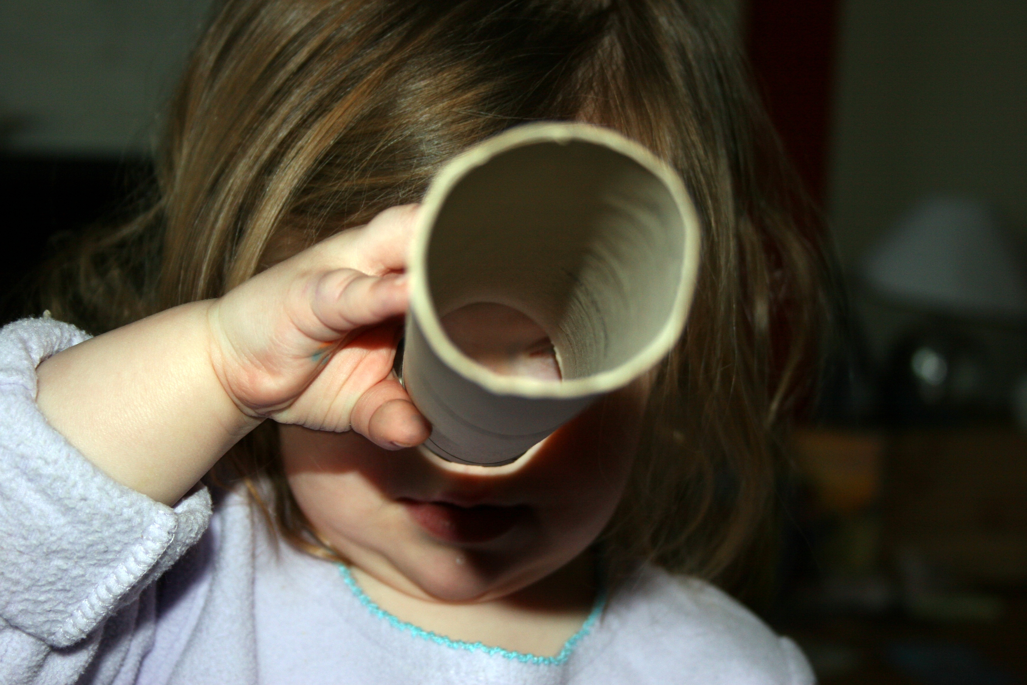 little girl looking through paper towel roll